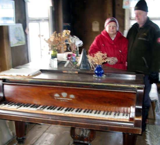 Vanha flyygeli on edelleen nyt jo autioituneessa Huoisen tuvassa. Soittimen äärellä Helga ja Arvi Karvonen.