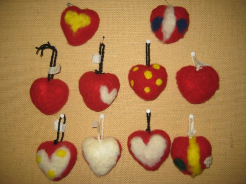3-4 luokkalaisten neulahuovutuksella koristellut sydämet.