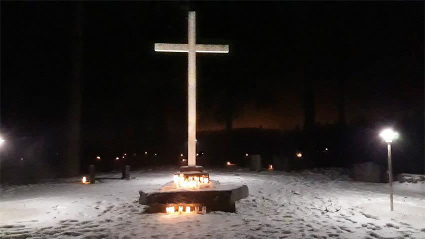 Kuvassa on Värtsilän Leminrinteen kalmismaan suurikokoinen risti Pyhäinpäivän iltahämärässä 2019